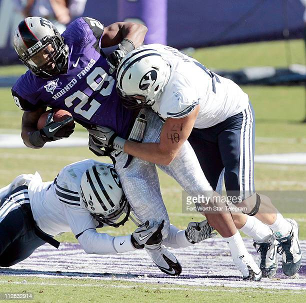 Texas Christian tailback Matthew Tucker is brought down by Brigham Young's Jadon Wagner right and Andrew Rich at Amon G Carter Stadium in Fort Worth...