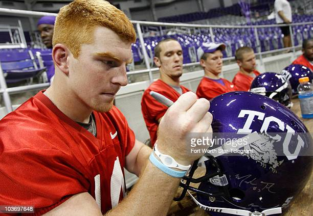 Texas Christian University quarterback Andy Dalton autographs a helmet for a fan during an event where fans got to meet and get autographs from...