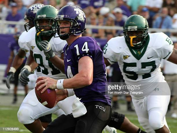 Texas Christian University quarterback Andy Dalton looks ot pass under pressure from the Baylor defense during the first quarter at Amon Carter...