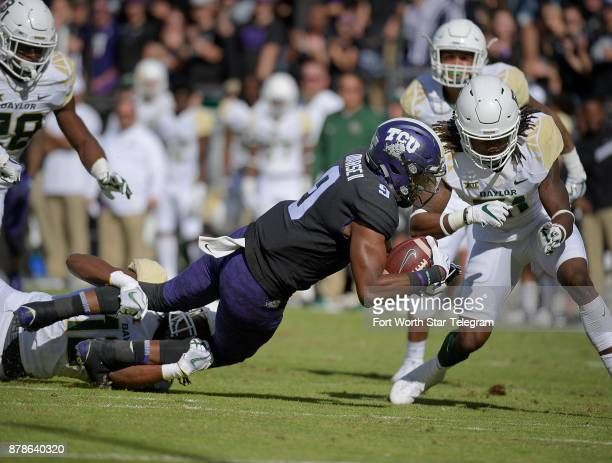 Texas Christian wide receiver John Diarse picks up a first down during the first quarter dragging Baylor safety Davion Hall and before colliding with...