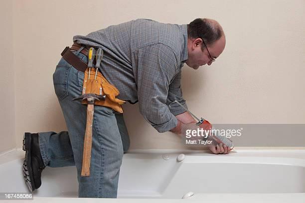 USA, Texas, Dallas, Man with Caulk Gun working in bathroom