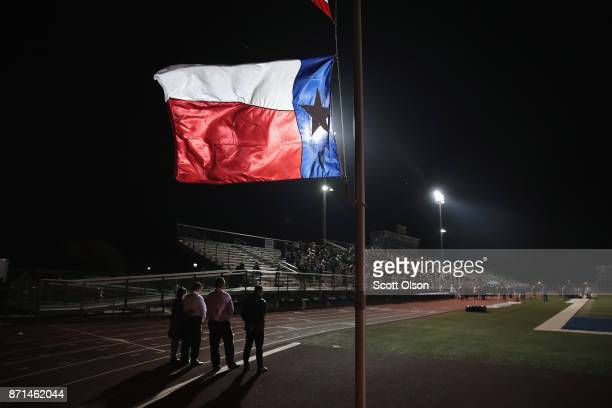 Texas flag flies at half mast during a prayer services at the La Vernia High School Football stadium to grieve the 26 victims killed at the First...