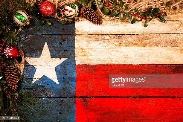 Texas flag, wooden. Christmas decorations, pine cones, ornaments, holly, garland.