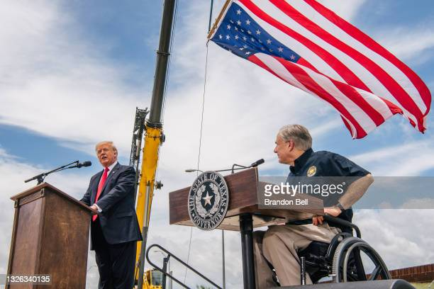Texas Gov. Greg Abbott listens to former President Donald Trump's address during a tour to an unfinished section of the border wall on June 30, 2021...