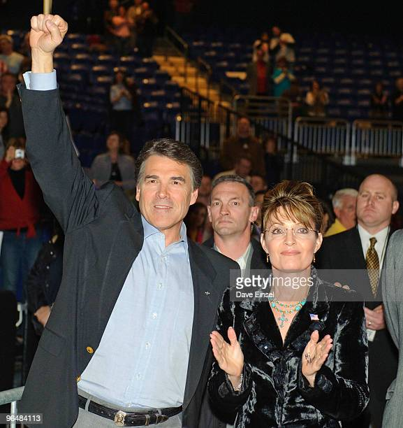 Texas Gov Rick Perry reacts to the crowd as he waits to take the stage with former Alaska Gov Sarah Palin during a campaign rally for Perry February...