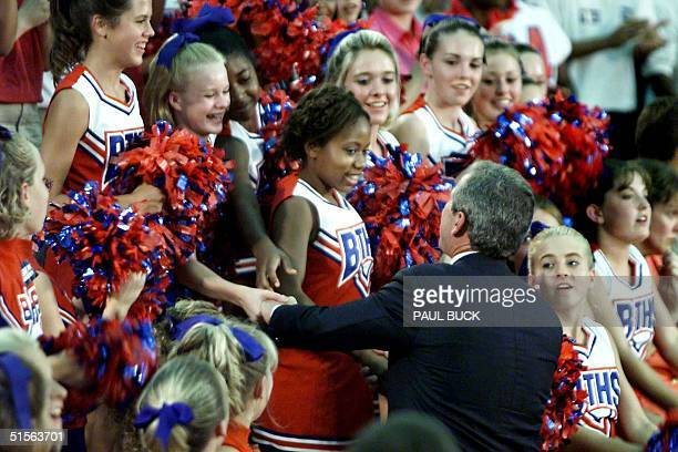 Texas Governor and presidential candidate George W Bush meets cheerleaders prior to his speech at Butler Traditional High School in Louisville...