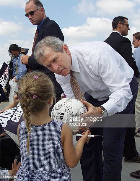 Texas Governor and Republican presidential candidate George W. Bush signs a soccer ball for four-year-old Jessie Rogers at Springfield/Branson...