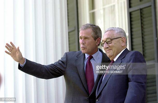 Texas Governor and Republican presidential candidate George W. Bush waves to journalists as he stands next to Henry Kissinger at a porch in the...