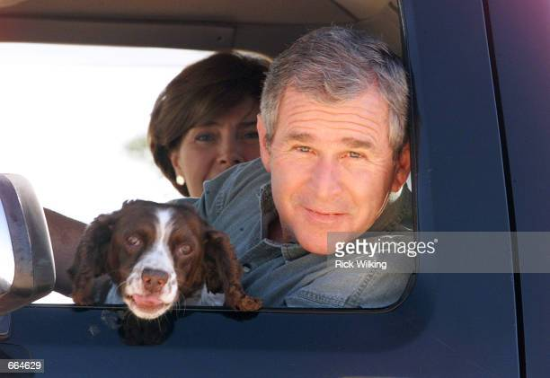 Texas Governor and Republican presidential candidate George W Bush and his wife Laura ride in the family pickup truck with their dog Spot the...