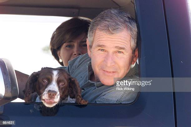 Texas Governor and Republican presidential candidate George W Bush and his wife Laura ride in the family pickup truck with their family dog Spot the...
