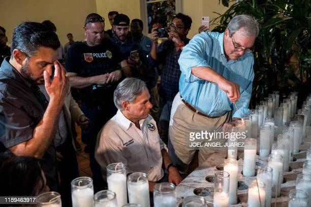 Texas Governor Greg Abbott and El Paso Mayor Dee Margo light candles after a vigil ceremony at Saint Pius X Church, following a deadly mass shooting,...