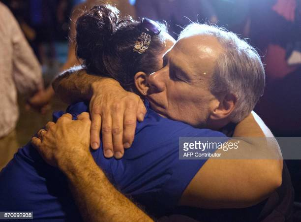 Texas Governor Greg Abbott comforts a local resident during a candlelight vigil held on November 5 following the mass shooting inside the First...