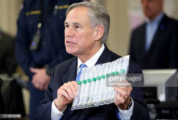 Texas Governor Greg Abbott displays COVID-19 test collection vials as he addresses the media during a press conference held at Arlington Emergency...