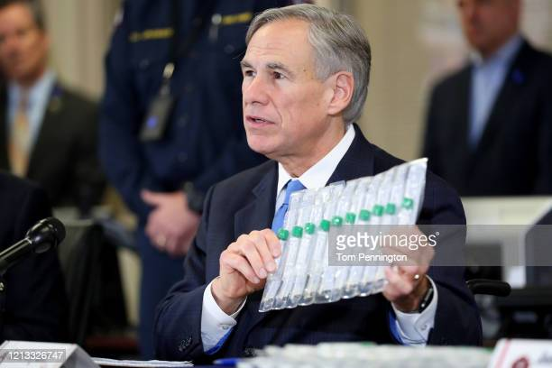 Texas Governor Greg Abbott displays COVID19 test collection vials as he addresses the media during a press conference held at Arlington Emergency...