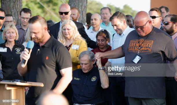 Texas Governor Greg Abbott holds hands with family and friends at a vigil held at the First Bank in Santa Fe for the victims of a shooting incident...