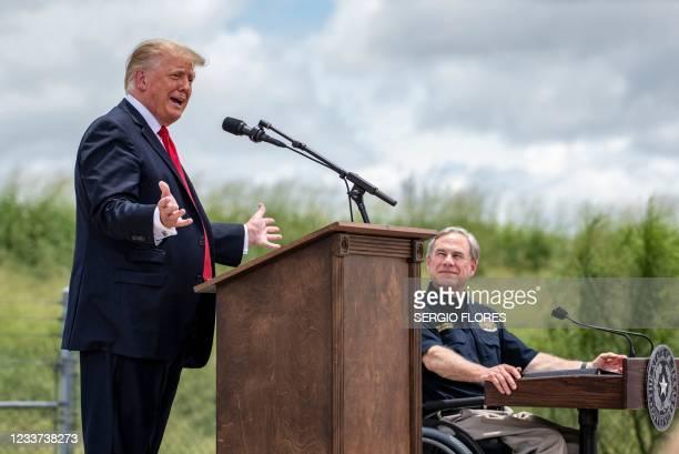 Texas Governor Greg Abbott listens as former US president Donald Trump speaks during a visit to the border wall near Pharr, Texas on June 30, 2021. -...