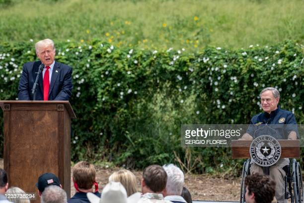 Texas Governor Greg Abbott looks on as former US president Donald Trump speaks during a visit to the border wall near Pharr, Texas on June 30, 2021....