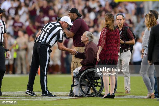 Texas Governor Greg Abbott shakes hand with an official before the college football game between the South Carolina Gamecocks and the Texas AM Aggies...
