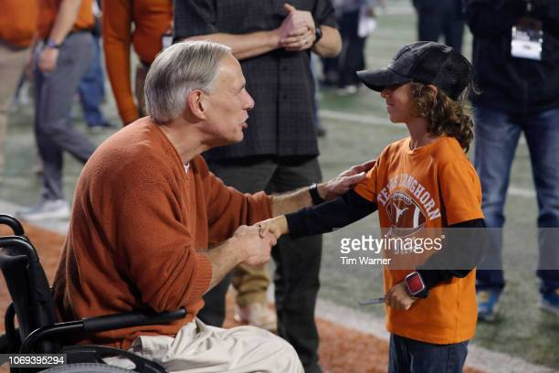 Texas Governor Greg Abbott shakes hands with a young fan after the game against the Iowa State Cyclones at Darrell K RoyalTexas Memorial Stadium on...