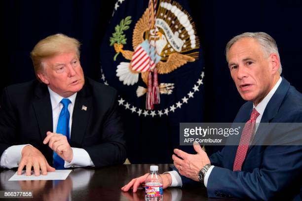 Texas Governor Greg Abbott speaks with US President Donald Trump during a briefing on hurricane relief efforts in Dallas, Texas, on October 25, 2017....