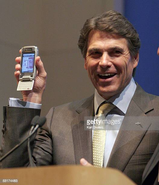 Texas Governor Rick Perry smiles after being presented with a new Ericsson cellular phone by Ericsson North America President Angel Ruiz during a...