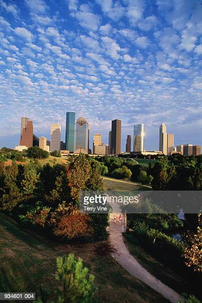 usa, texas, houston, skyline, two men jogging through park in fore - houston stock pictures, royalty-free photos & images