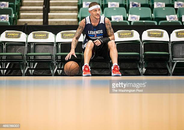 Texas Legends basketball player Delonte West dribbles a basketball in a sitting position while watching a pregame dance routine performed by local...
