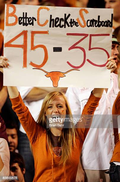 Texas Longhorn fan cheers on her team against the Texas AM Aggies while holding a reminder of the Texas score against Oklahoma earlier in the season...