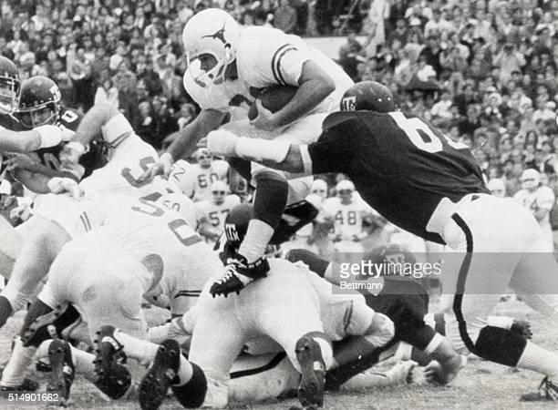 Texas Longhorn halfback Billy Dale hurdles the Texas Aggie line for a pickup of 7 yards to the Aggie 37 in the first period of play Making the stop...