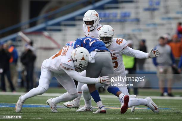 Texas Longhorns linebacker Anthony Wheeler and defensive back Caden Sterns tackle Kansas Jayhawks running back Dom Williams during the first half of...