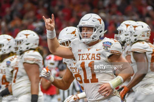 Texas Longhorns quarterback Sam Ehlinger gives the roaring Texas crowd a Hook 'em Horns sign after scoring a first half rushing touchdown during the...