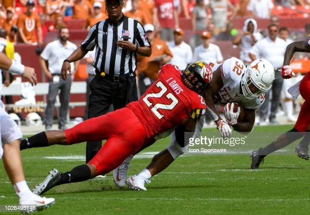 Texas Longhorns running back Daniel Young is tackled by Maryland Terrapins linebacker Isaiah Davis on September 1 at FedEx Field in Landover MD The...