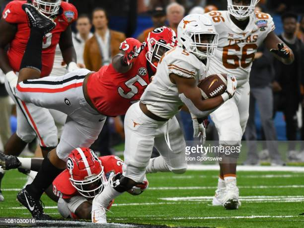 Texas Longhorns Running Back Tre Watson rushes the ball as Georgia Bulldogs Linebacker Tae Crowder and Georgia Bulldogs Defensive Linemen Tyler Clark...