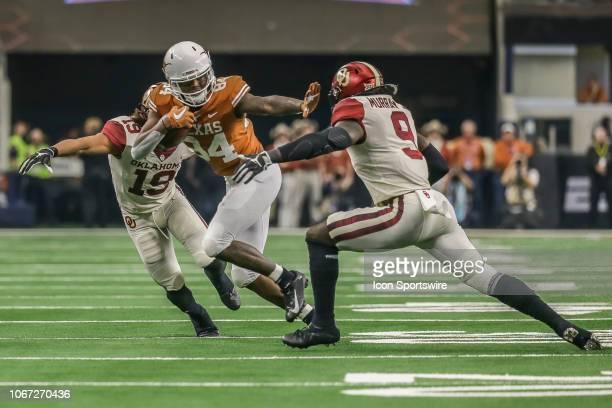 Texas Longhorns wide receiver Lil'Jordan Humphrey stiffarms Oklahoma Sooners linebacker Kenneth Murray during the game between the Texas Longhorns...