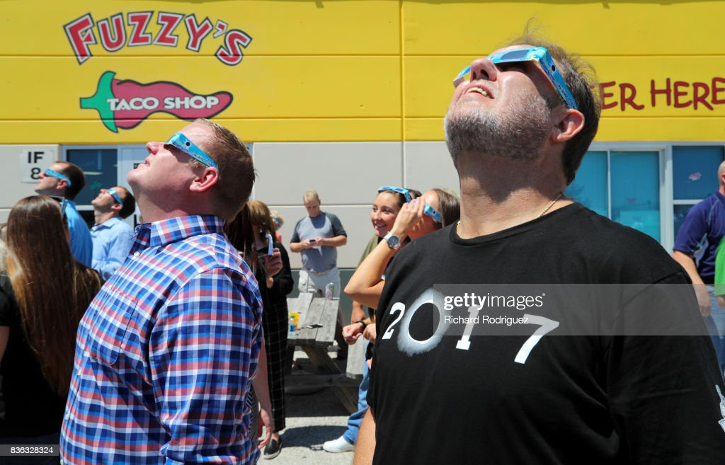 Texas Motor Speedway President Eddie Gossage (R) and other TMS staff use eclipse glasses to watch the solar eclipse at a party at Fuzzy's Tacos at Texas Motor Speedway on August 21, 2017 in Fort Worth, Texas. Millions of people have flocked to areas of the U.S. that are in the 'path of totality' in order to experience a total solar eclipse. During the event, the moon will pass in between the sun and the Earth, appearing to block the sun. Fort Worth residents will see about 75 percent of the sun blocked by the moon.