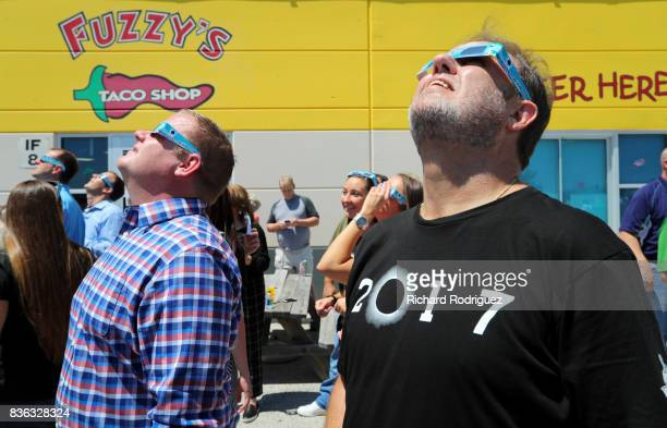 Texas Motor Speedway President Eddie Gossage and other TMS staff use eclipse glasses to watch the solar eclipse at a party at Fuzzy's Tacos at Texas...