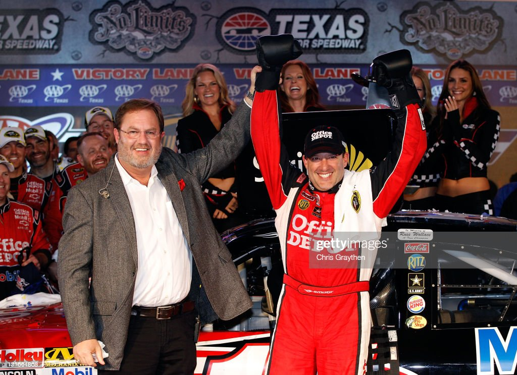 Texas Motor Speedway president Eddie Gossage (L) poses with Tony Stewart, driver of the #14 Office Depot/Mobil 1 Chevrolet, in Victory Lane after winning the NASCAR Sprint Cup Series AAA Texas 500 at Texas Motor Speedway on November 6, 2011 in Fort Worth, Texas.
