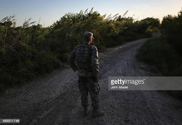 Texas National Guard soldier monitors a road near the USMexico border on September 11 2014 in Havana Texas His unit deployed near the Rio Grande is...