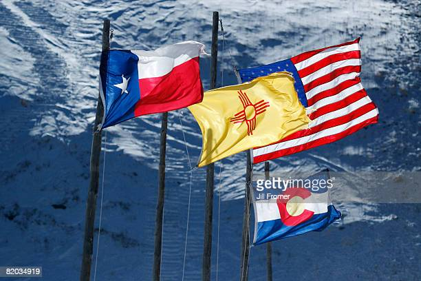Texas, New Mexico, Colorado and American flags flying against a snow covered mountain background.