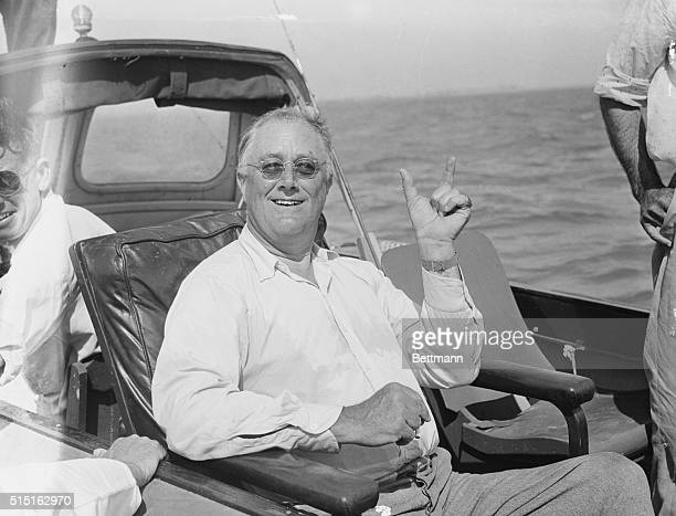 President Roosevelt Tells A Fish Story President Franklin Roosevelt is shown above as he tells a fish story to the members of his party aboard a...