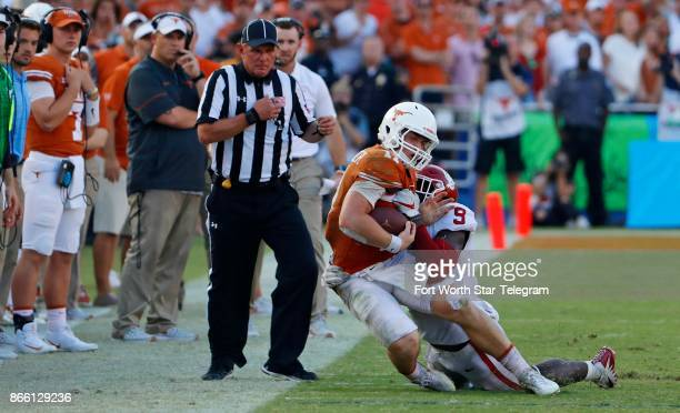 Texas quarterback Sam Ehlinger is hit at the sidelines by Oklahoma linebacker Kenneth Murray in the fourth quarter of the Red River Showdown at the...
