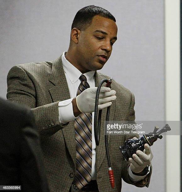 Texas Ranger David Armstrong holds a bong part of the evidence seized at Eddie Ray Routh's house during the capital murder trial of former Marine Cpl...