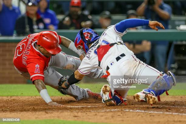Texas Rangers Catcher Robinson Chirinos attempts to tag Los Angeles Angels Catcher Martin Maldonado at the plate but Maldonado is called safe after a...