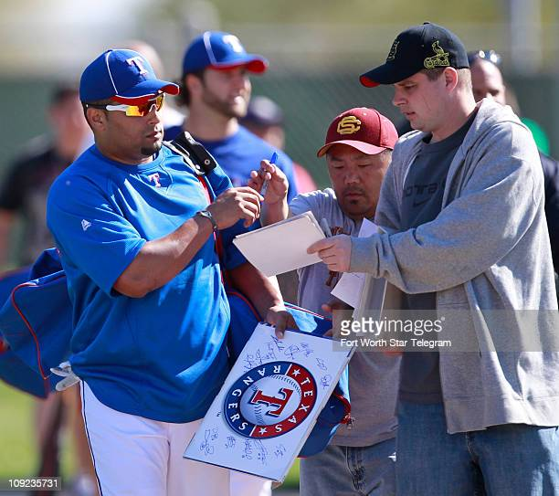 Texas Rangers catcher Yorvit Torrealba signs for autograph seekers Thursday morning during spring training in Surprise Arizona February 17 2011