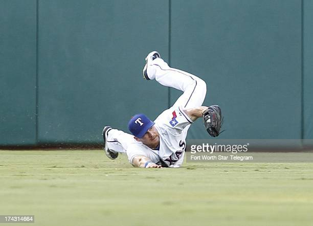 Texas Rangers center fielder Craig Gentry dives and catches a fly ball hit by New York Yankees' Lyle Overbay not shown during the third inning at...
