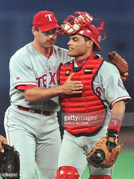 Texas Rangers closing pitcher John Wetteland pats catcher Ivan Rodriguez after Wetteland went 11 hitless inning in relief and recorded his first save...