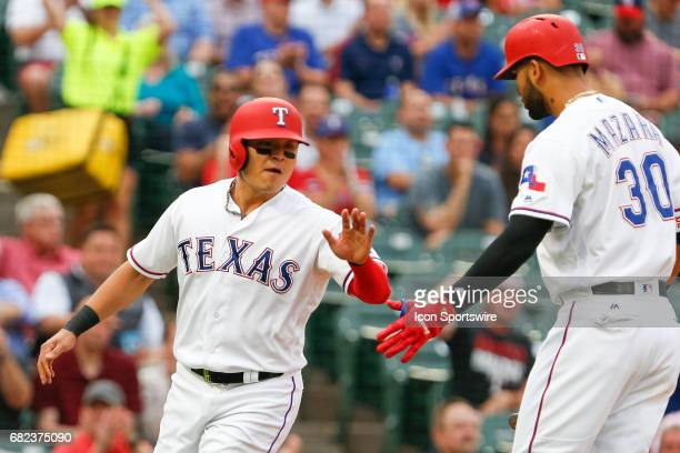 Texas Rangers Designated hitter ShinSoo Choo slaps hands with Nomar Mazara after scoring on a wild pitch during the MLB game between the San Diego...