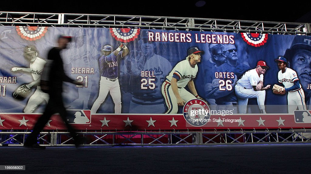 A Texas Rangers fan walks past a mural of past team legends at the team's Fan Fest in the Arlington Convention Center on Saturday, January 12, 2013, in Arlington, Texas.