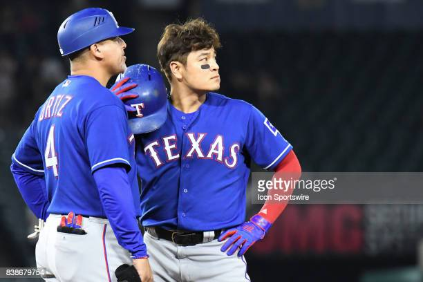 Texas Rangers first base coach Hector Ortiz and Texas Rangers Designated hitter ShinSoo Choo watch the replay on vision board as a potential game...