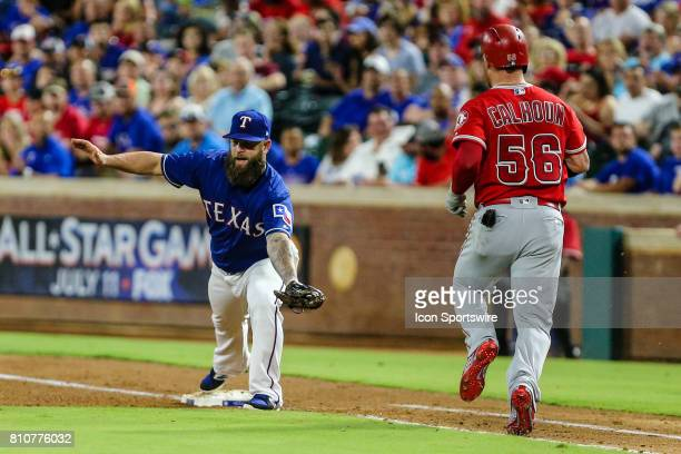 Texas Rangers first baseman Mike Napoli stretches for the ball for an out over Los Angeles Angels right fielder Kole Calhoun during the game between...